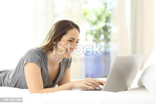 istock Happy lady using a laptop on the bed at home 1061387366