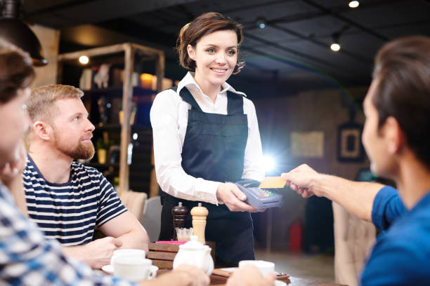 happy lady waitress holding card reader while guest paying with - paying with card contactless imagens e fotografias de stock