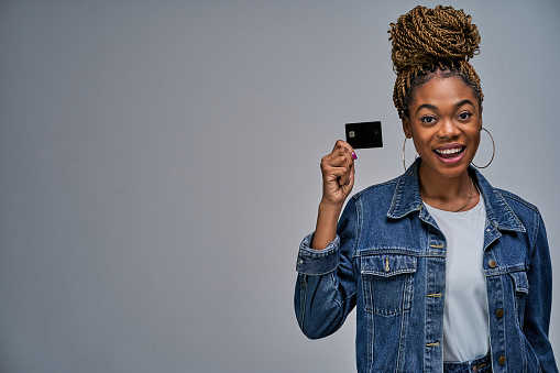 istock Happy lady with bun in a jeans jacket shows a black bank credit card in her hand. Banking concept 1217051968