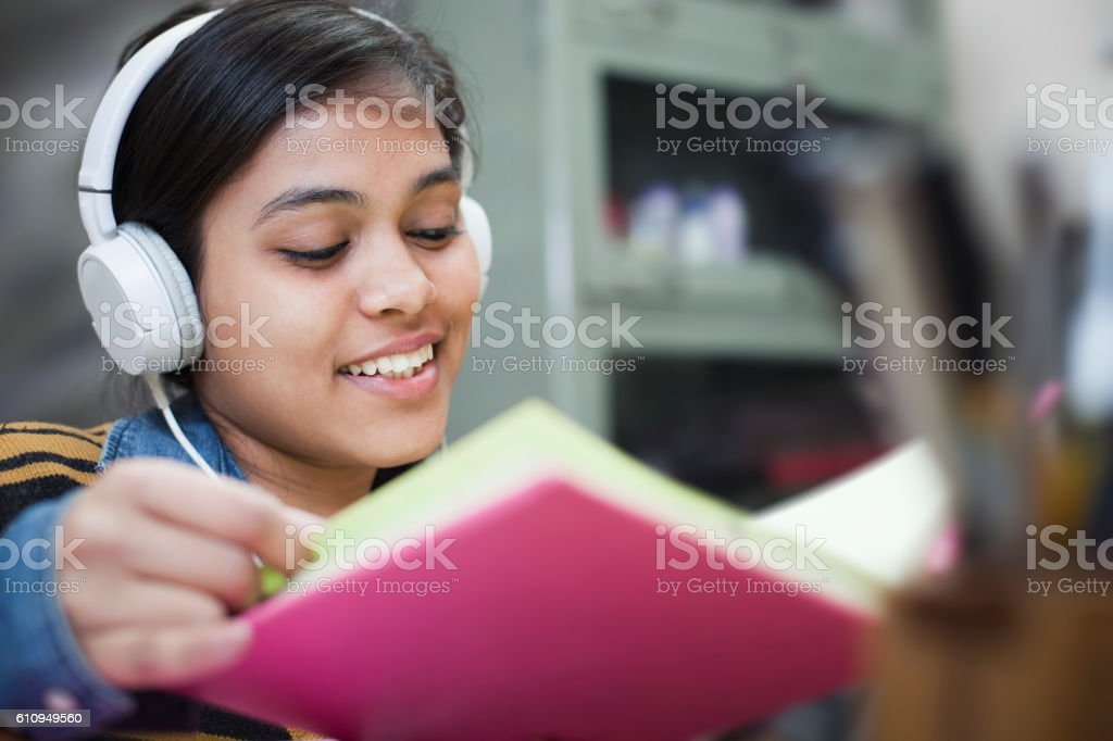 Happy late teen girl student studying and listening music. stock photo