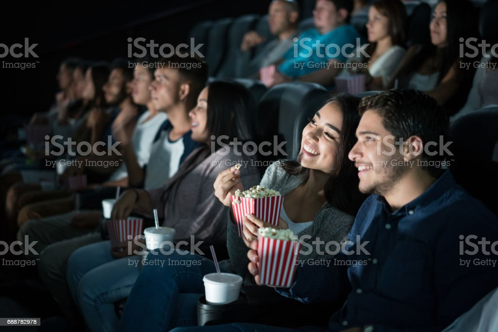 Happy Latin American couple at the movies stock photo