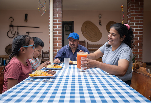 Happy Latin American family having lunch together at home - developing countries lifestyle concepts