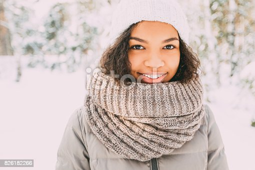 istock Happy Latin American girl in knit hat and scarf 826182266