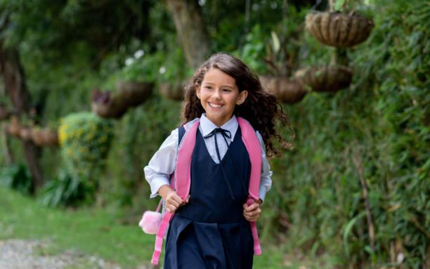 Glückliches lateinamerikanisches Mädchen, das in ihrer Uniform zur Schule geht – Foto