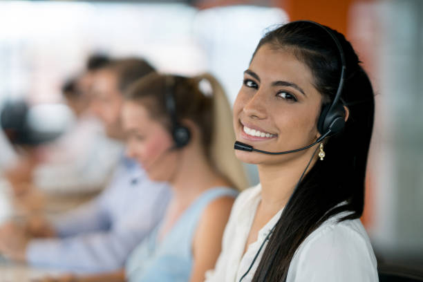 happy latin american woman working at a call center - switchboard operator stock photos and pictures