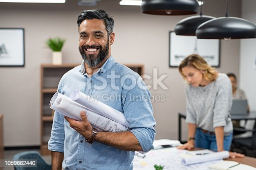 istock Happy latin architect holding blueprints 1059662440