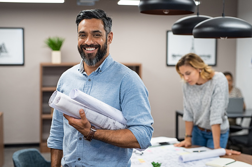 Portrait of multiethnic architect with blueprints in creative office. Mature middle eastern contractor holding roll of architectural projects while looking at camera. Happy latin man in casual standing in meeting room with engineers working in background.