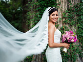 Happy latin bride with long veil looking away