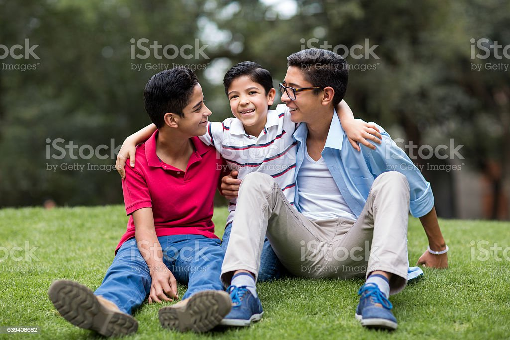 Happy latin brothers sitting and smiling at each other - foto de stock