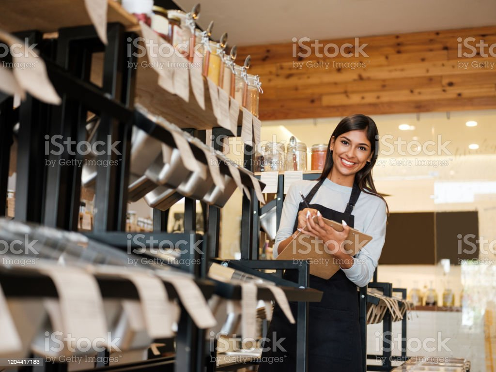 Happy latin employee holding clipboard and smiling at camera A happy latin female employee working in an eco-friendly shop, holding a clipboard and smiling at the camera. 20-29 Years Stock Photo