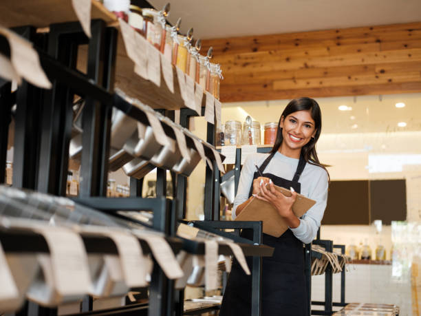 Happy latin employee holding clipboard and smiling at camera stock photo