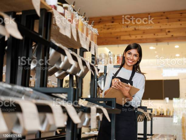 Happy Latin Employee Holding Clipboard And Smiling At Camera Stock Photo - Download Image Now