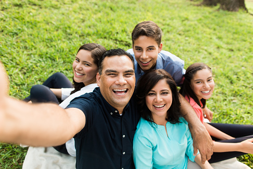 A happy latin family of five taking a selfie and smiling in a horizontal medium shot outdoors.
