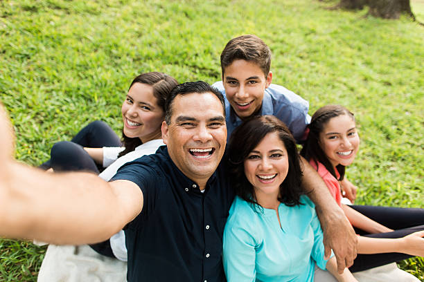 Happy latin familly taking a selfie outdoors stock photo
