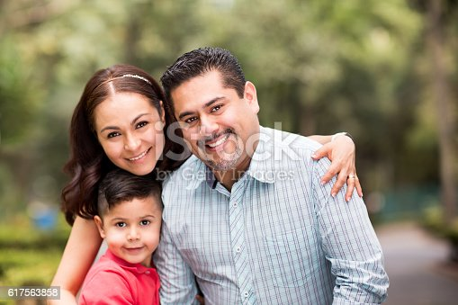 istock Happy latin family with one child smiling at camera 617563858