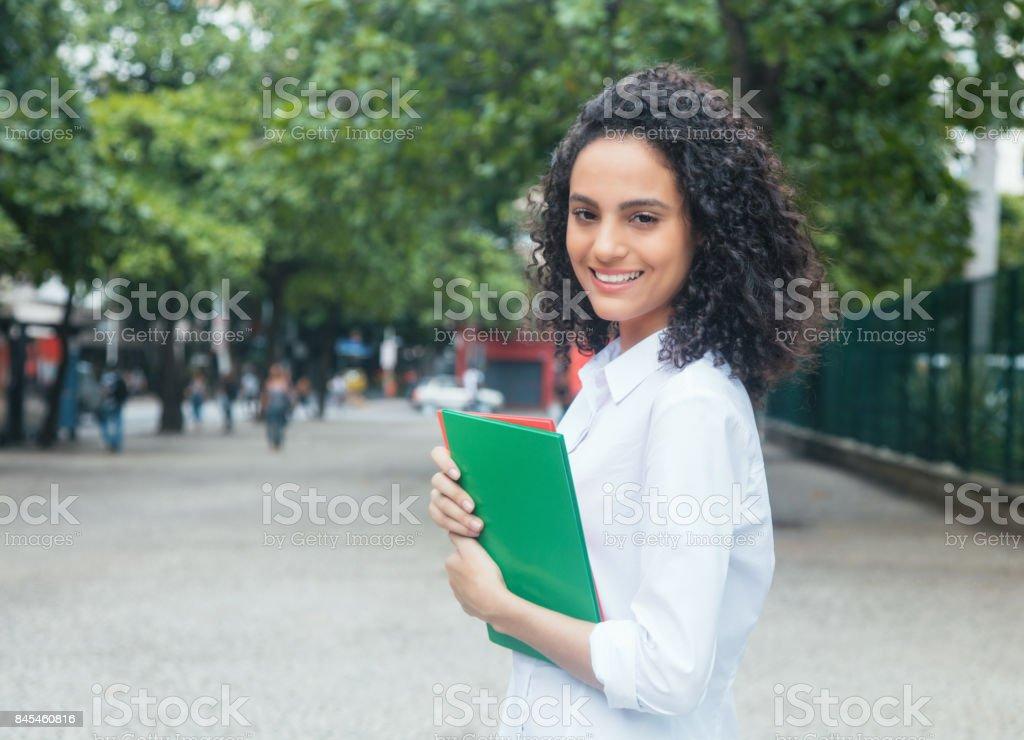 Estudante de latim feliz com cabelo encaracolado e camisa branca - foto de acervo