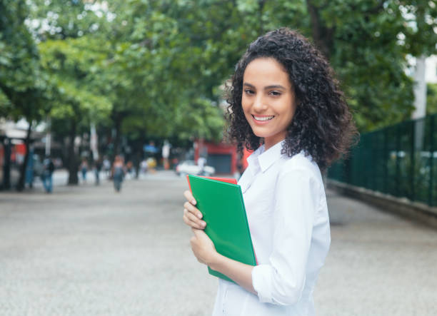 Happy latin female student with curly hair and white shirt stock photo
