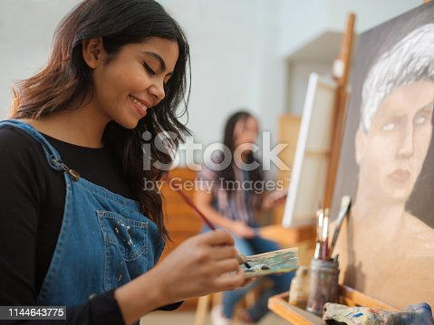 A latin female smiling as she uses a paintbrush to mix colors on a palette while standing in front of her painting.