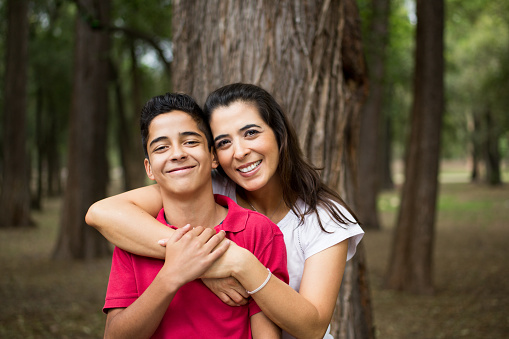 Happy latin mother and teen son embracing and smiling