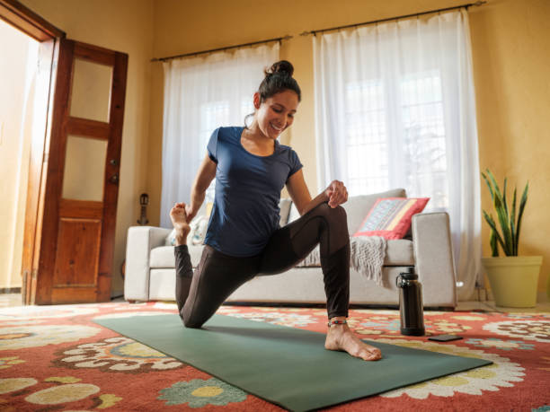 Happy latin woman stretching legs on mat in living room stock photo