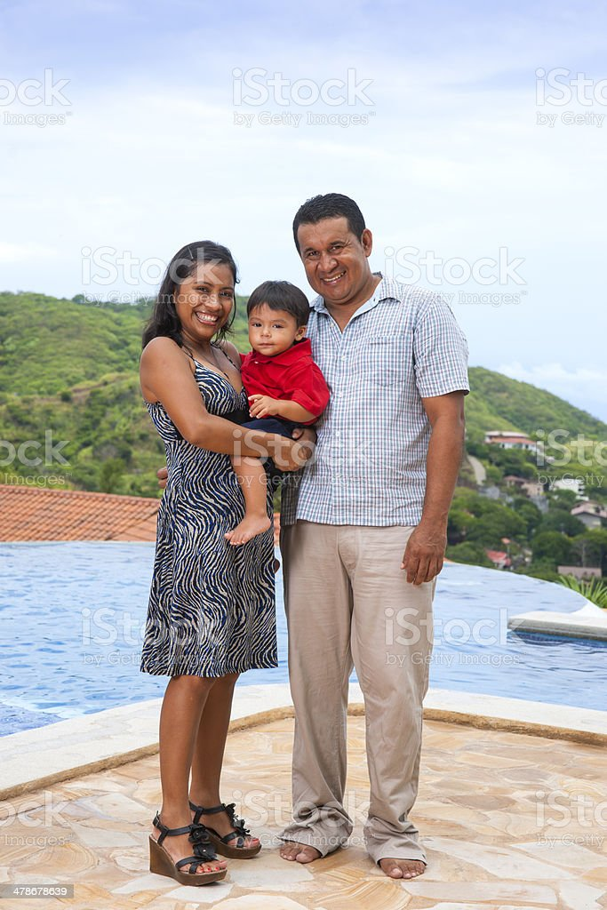 Happy Latino family by a swimming pool. stock photo