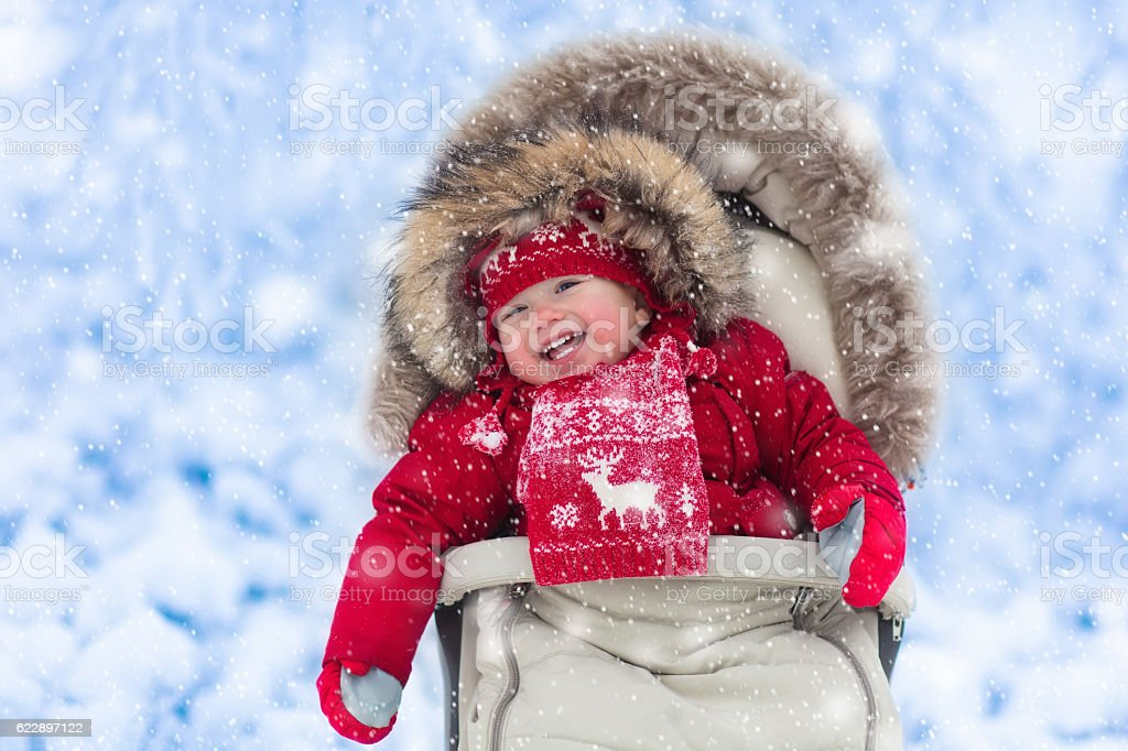 Happy laughing aby in stroller in winter park with snow stock photo