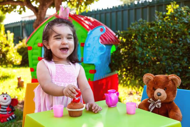 glücklich lachendes baby kleinkind mädchen in outdoor-zweiten geburtstag party kerze halten. - mädchen spielhaus stock-fotos und bilder
