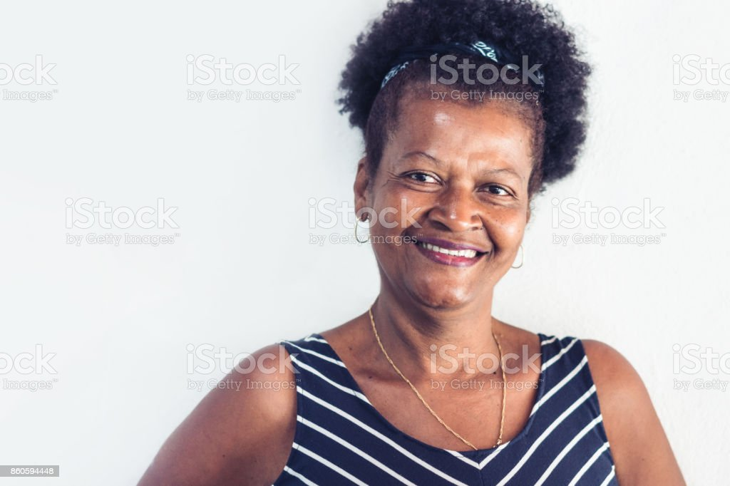 Happy laughing brazilian woman in front of white wall stock photo