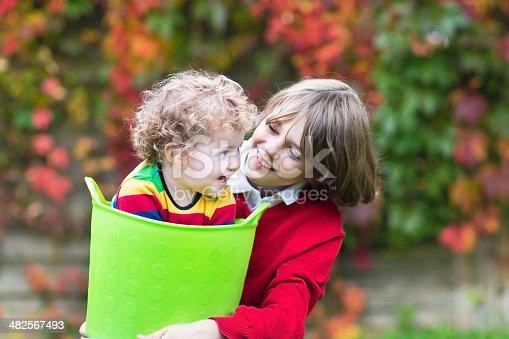 954356678istockphoto Happy laughing brother and baby sister playing with laundry basket 482567493