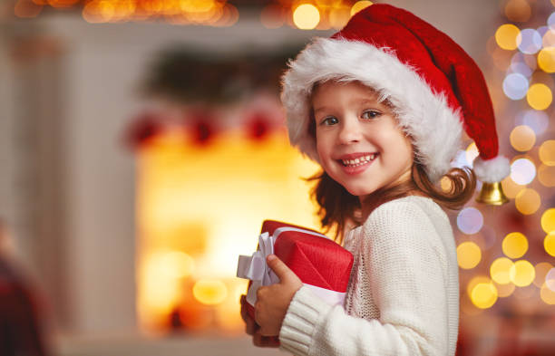 happy laughing child girl with christmas present at home - christmas background стоковые фото и изображения