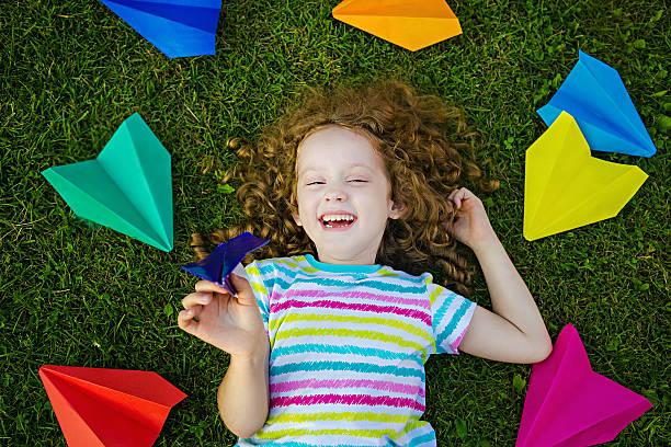 Feliz sorrindo menina jogando Aviãozinho-de-papel - foto de acervo