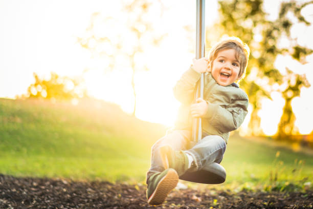 happy laughing little boy on zipline in bright sunshine stock photo