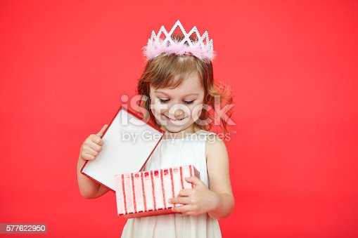 istock Happy laughing little girl opening a gift box 577622950