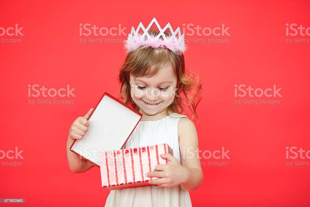 Happy laughing little girl opening a gift box stock photo