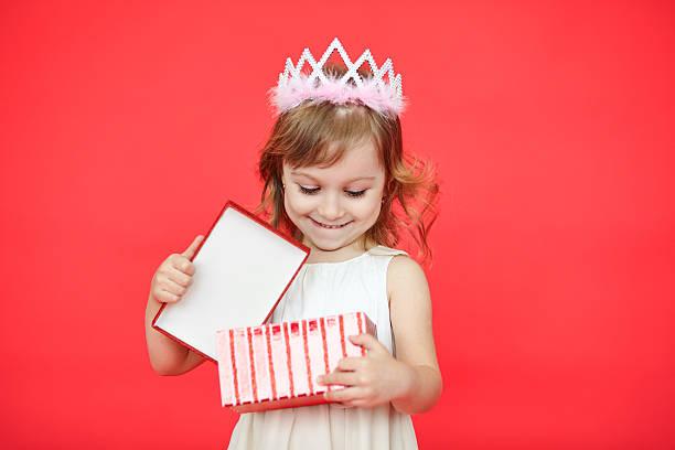 happy laughing little girl opening a gift box - jugendliche geburtstag geschenke stock-fotos und bilder
