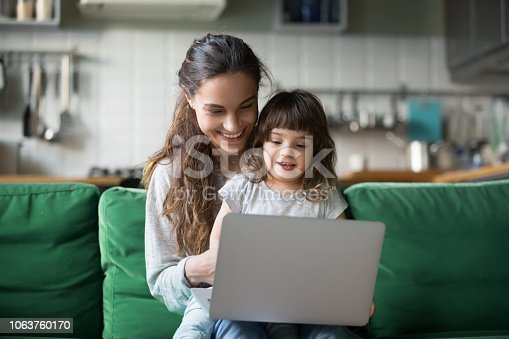 1063760138 istock photo Happy laughing mother and daughter using laptop 1063760170