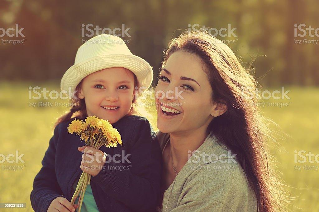 Feliz risa madre que enaltece su hija con amarillo brillante foto de stock libre de derechos