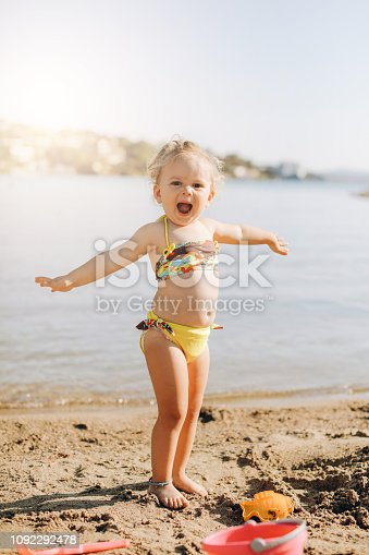Happy laughing toddler girl having fun on sand