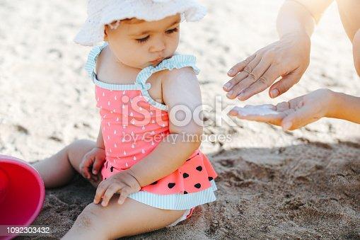 Happy laughing toddler girl having fun on sand
