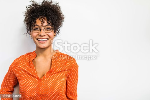 Pretty biracial woman in orange shirt portrait against a white wall
