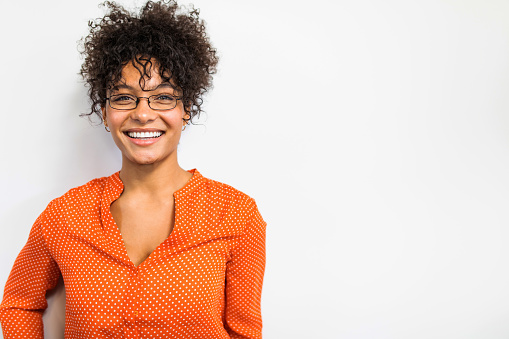Pretty biracial woman in orange shirt portrait against a white wall