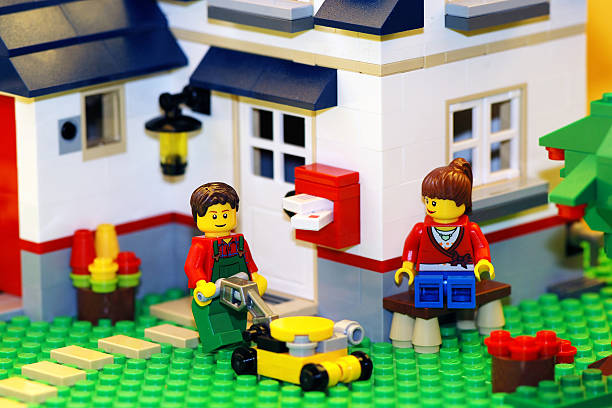 happy lego couple with new house - lego house stock photos and pictures