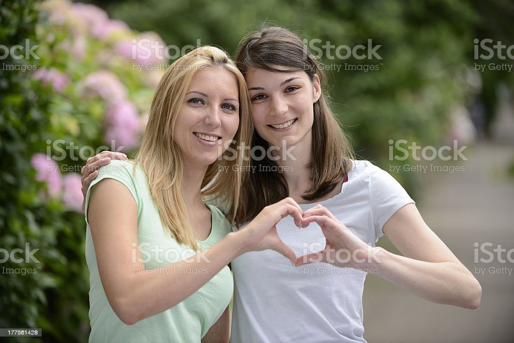 Happy lesbian couple forming heart with hands royalty-free stock photo