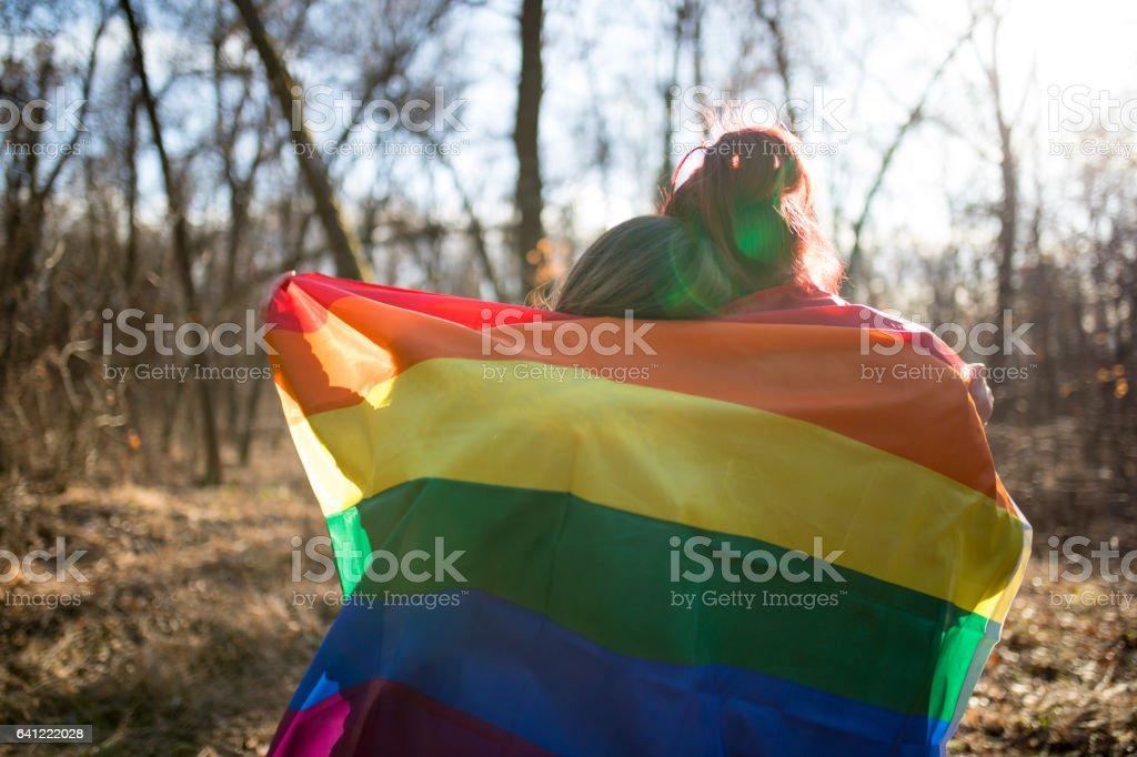 Happy lesbian couple holding rainbow flag stock photo