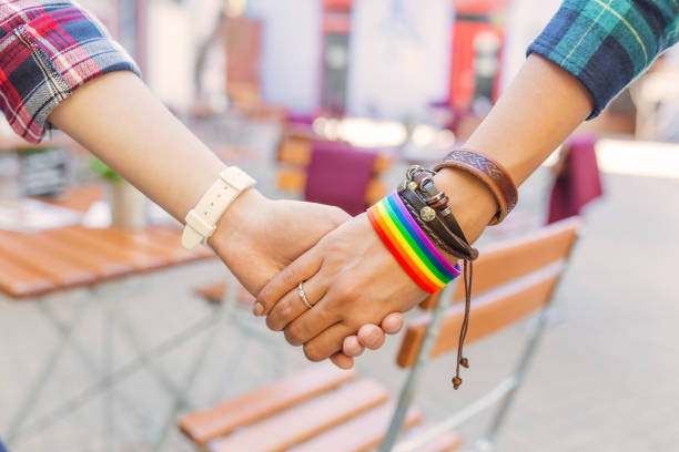Happy lesbian couple wearing rainbow bracelet Happy lesbian couple wearing rainbow bracelet lgbtqi rights stock pictures, royalty-free photos & images