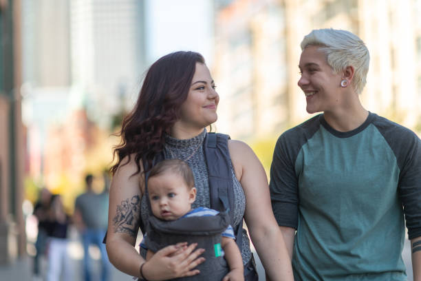 Happy lesbian couple with baby walking in city A young adult LGBT couple is spending time together. The partners are walking with their baby in the city. It's a sunny day. The cisgender adult is holding the child in a baby carrier. The couple is holding hands and smiling. cisgender stock pictures, royalty-free photos & images