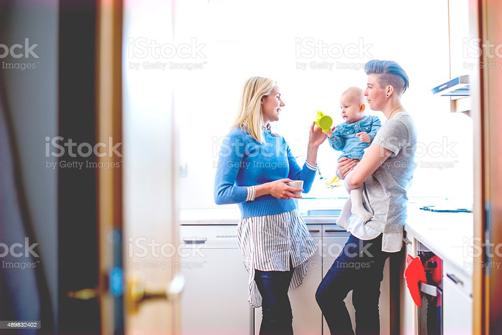 Happy lesbian women with baby in domestic room royalty-free stock photo