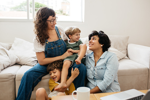 Happy lesbian couple playing with their children at home. Beautiful family of four having great time together indoors.