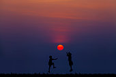 Happy life and successful concept. Silhouetted of children playing a red sun as basketball at sunset. Travel and freedom lifestyle. Picture for add text message. Backdrop for design art work.