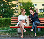 two friends sitting on bench in park and laughing, lifestyle concept, casual clothing. spring season.